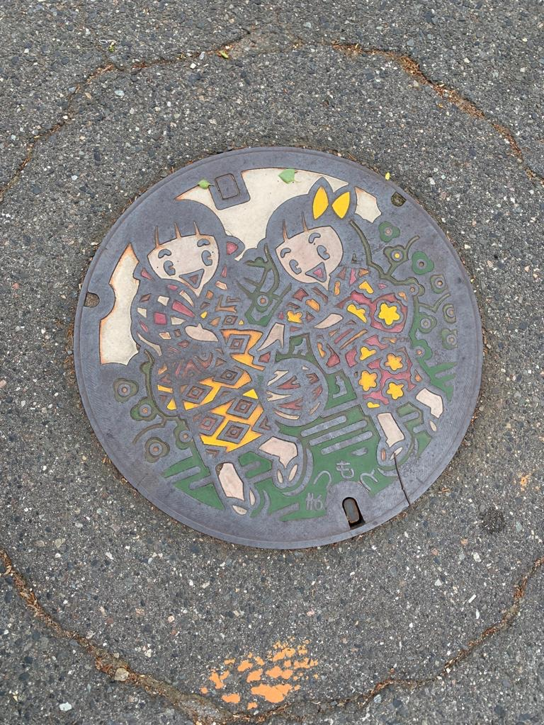 Colorful manhole cover showing two girls in kimonos, Matsumoto